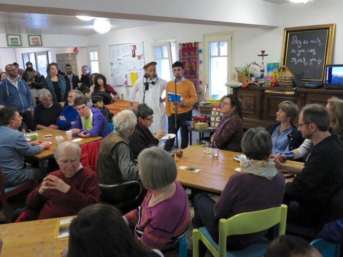 Im vollbesetzten Café Mondial berichteten Ramin (im orangen Pullover am Mikrofon) und Jalali über die politischen Verhältnisse in ihrem Heimatland. (Lutz Rauschnick)